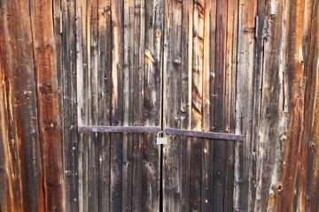 burnt wooden door locked with rusty padlock