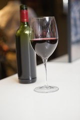 Close up of red wine into glass in front of the bottle