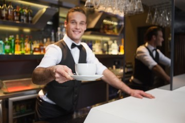 Smiling waiter offering cup of coffee smiling at camera