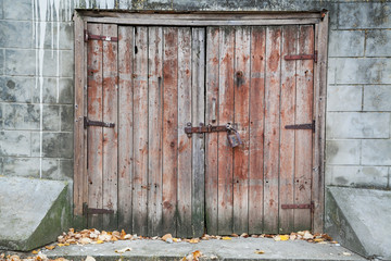 Old wooden barn door locked with padlock