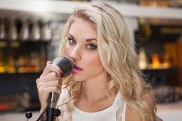 Young blonde woman singing while looking at camera