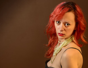 Portrait of a young woman with red hair looking at the camera