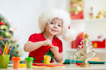 kid in Santa hat making christmas tree of plasticine