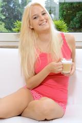 Frau in Nachtwäsche trinkt Kaffee
