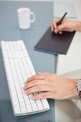 Designer using digitizer and typing on keyboard