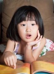 Asian little girl read her book aloud