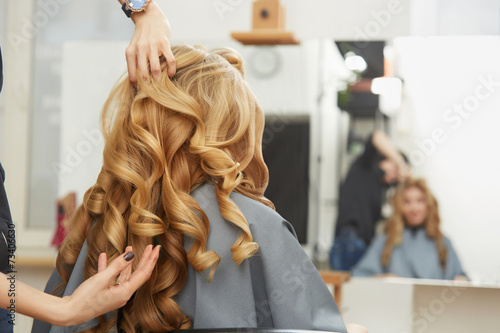 Blonde curly hair. Hairdresser doing hairstyle for young woman i Poster