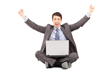 Happy businessman working on a laptop