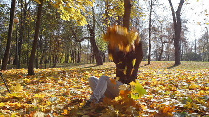 Girl sits on the earth and throws fallen leaves up