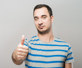 Handsome  man holds his thumbs up