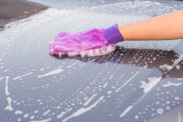 Closeup cleaning his car using gloves car wash