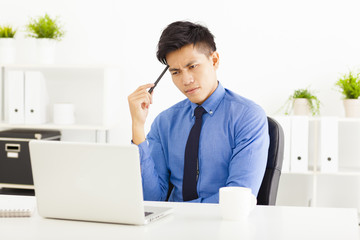 Young business man watching laptop and thinking