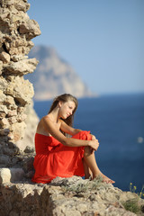 girl in red dress posing on the coast