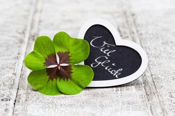 vierblättriges Kleeblatt und Herz auf Holz, Viel Glück