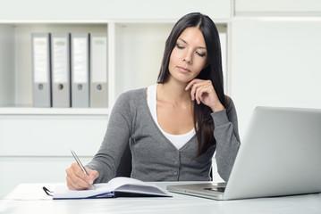 Ernste junge Frau arbeitet an ihrem Schreibtisch