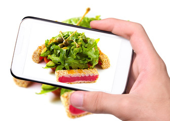 Hands taking photo fish with salad with smartphone