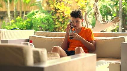 Young teenager talking on cellphone and drinking soda at home