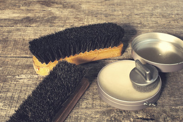 Shoe wax and brushes on wooden surface