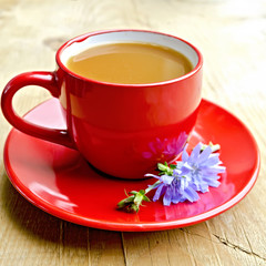 Chicory drink in red cup with flower on board