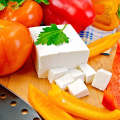 Feta with vegetables and herbs on wooden board