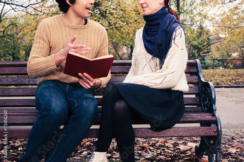 Man reading for woman on park bench