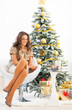 Full length portrait of happy woman sitting near christmas tree