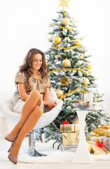 Full length portrait of happy woman sitting near christmas tree