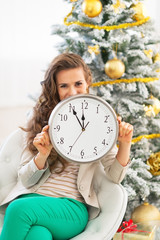 Young woman showing clock near christmas tree
