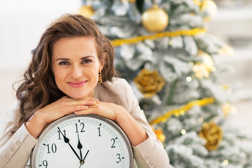 Happy young woman showing clock near christmas tree