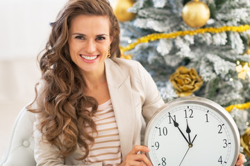 Smiling young woman showing clock near christmas tree