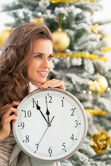 Profile portrait of smiling woman with clock near christmas tree