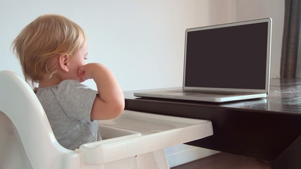 blonde baby touching blank screen pc