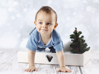 Little crawling baby boy with christmas tree