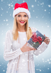 Beautiful woman with santa hat in his hand a gift