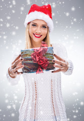 Woman with santa hat holding a gift to you