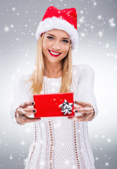Woman with santa hat holding a small red gift box