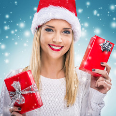 Woman with santa hat, holding two red gift box - snowfall