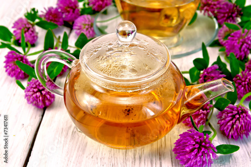 Tea with clover in glass teapot on light board - 73417611