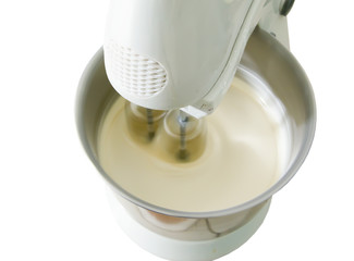 beating of the dough by electric mixer on white background