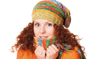 Freezing young woman hiding behind her scarf