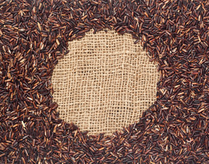 Red rice forming a round frame on burlap fabric
