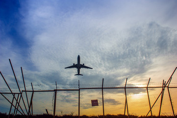 An airplane flying over barbed wire fence in Phuket airport