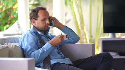 Young, handsome businessman talking on cellphone and drinking te