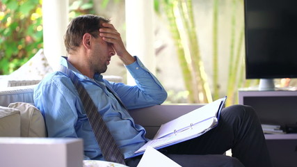 Businessman overwhelmed by bad news in documents sitting on sofa