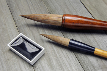 asian writing brushes and black ink for calligraphy on wooden