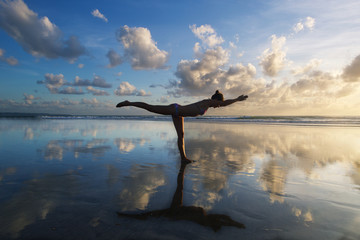 Young woman practicing warrior pose from yoga on the beach