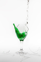 Green water spill from a broken wine glass on white background