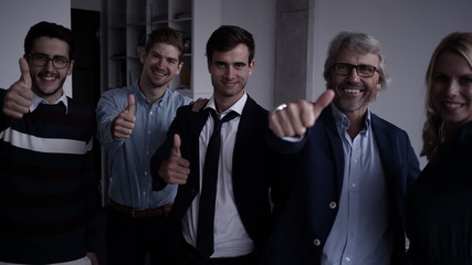 Positive office workers showing thumbs up to camera