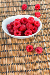 Decoration with raspberry fruits on a bamboo mat