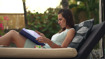 Serious businesswoman reading documents while lying on sunbed
